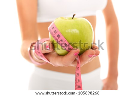 A picture of a young fit woman showing a green apple and a measure tape over white background - stock photo