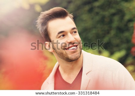 A picture of a young happy man in the park in autumn