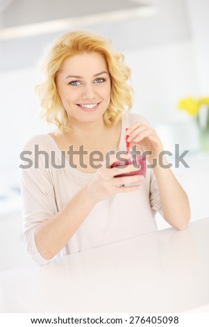 A picture of a young happy woman drinking smoothie in the kitchen