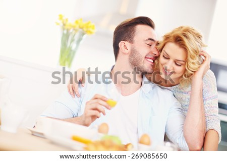 A picture of a young happy woman giving good morning hug to her husband - stock photo