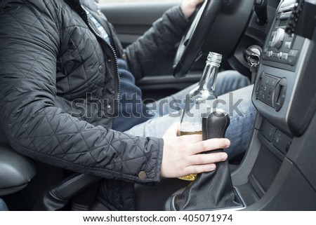 a picture of a young man drinking alcohol while driving - stock photo