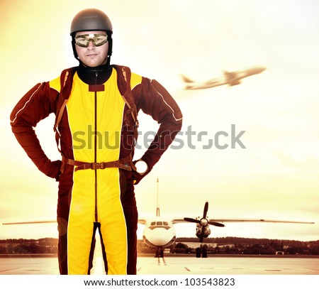A picture of a young parachutist standing in front of a plane at the apron
