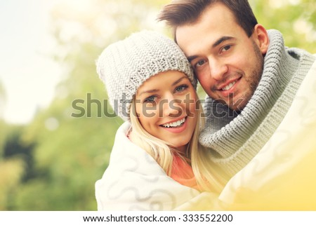A picture of a young romantic couple covered with blanket in the park in autumn - stock photo
