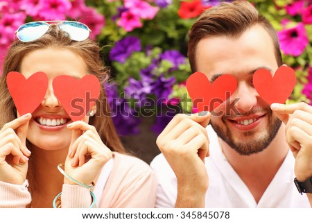 A picture of a young romantic couple covering eyes with hearts  - stock photo