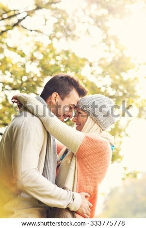 A picture of a young romantic couple hugging in the park in autumn - stock photo