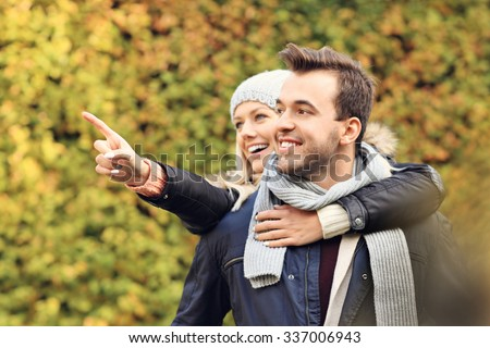 A picture of a young romantic couple pointing at something in the park in autumn