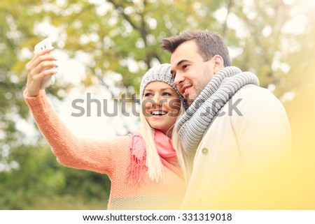 A picture of a young romantic couple with smartphone in the park in autumn - stock photo