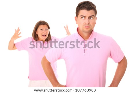 A picture of a young sad man standing over white background and his wife shouting in the back
