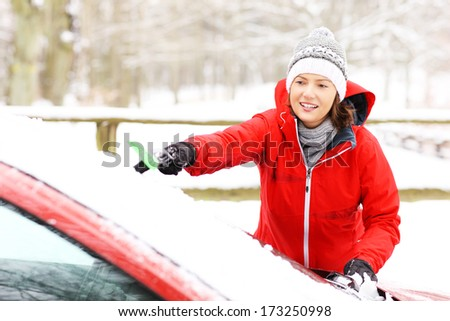 A picture of a young woman cleaning a windshield from the snow