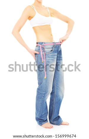 A picture of a young woman in loose jeans showing effects of diet over white background - stock photo