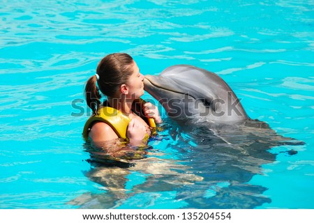 A picture of a young woman kissing a dolphin in a turquise water - stock photo