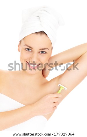 A picture of a young woman shaving her armpit over white background - stock photo