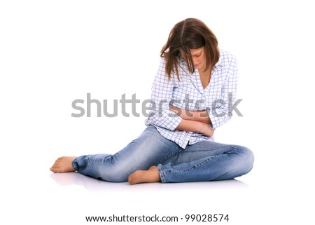 A picture of a young woman sitting on the floor and suffering from stomach ache - stock photo