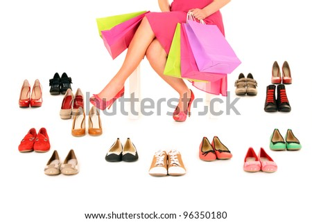 A picture of a young woman sitting with shopping bags among shoes over white background - stock photo