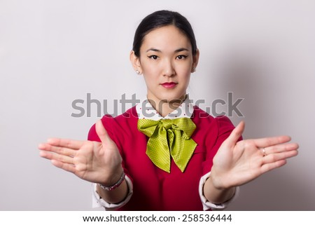 A picture of an attractive Asian stewardess showing emergency exits - stock photo