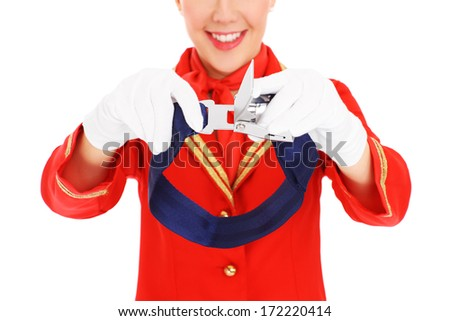 A picture of an attractive stewardess presenting a seat belt fastening over white background - stock photo