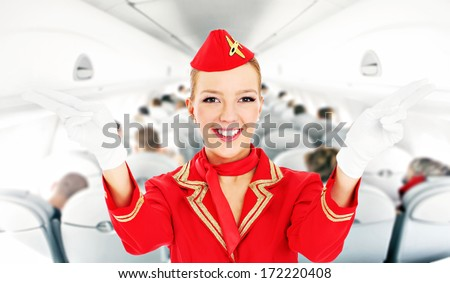 A picture of an attractive stewardess showing emergency exits in a plane - stock photo