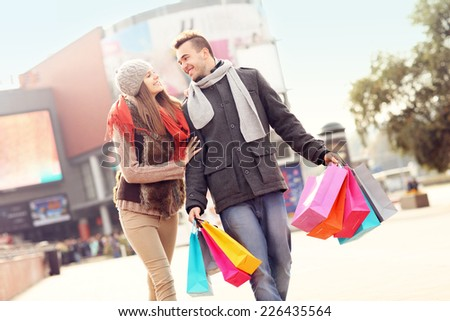 A picture of cheerful young people walking with shopping bags in the city - stock photo