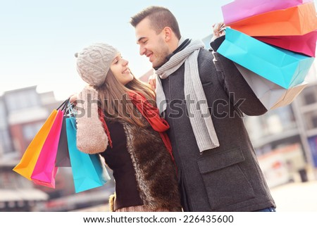A picture of cheerful young people with shopping bags in the city - stock photo