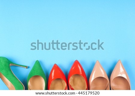 A picture of different shoes, Shot of several types of shoes, Several designs of  women shoes. Leather Shoe. Pile of various female shoes on on  light blue background. Copy space for text. - stock photo