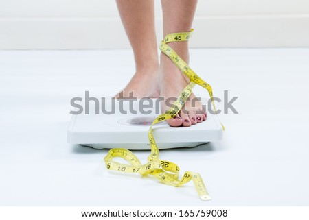 A picture of female feet standing on a bathroom scales and a tape measure  - stock photo