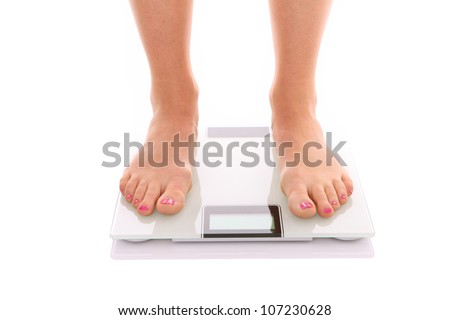 A picture of female feet standing on a bathroom scales over white background - stock photo