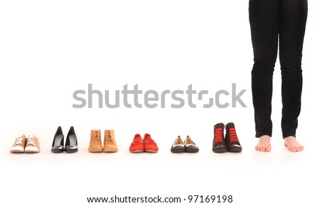 A picture of female legs among six pairs of shoes over white background - stock photo