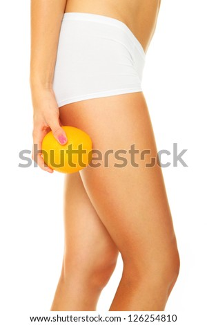 A picture of female legs and an orange over white background