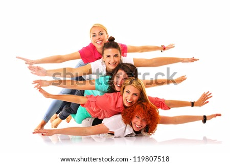 A picture of five joyful girls lying on each other and smiling over white background
