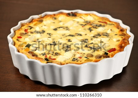 A picture of freshly baked vegetable quiche in a white tin over wooden surface - stock photo