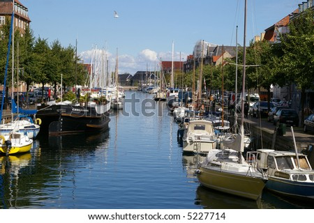 A picture of one of the canals Christianshavn, Copenhagen, Denmark. Numerous small vessels are docked along the canal lined by buildings.