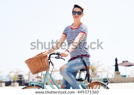 A picture of stylish young girl riding a bicycle in the city. - stock photo