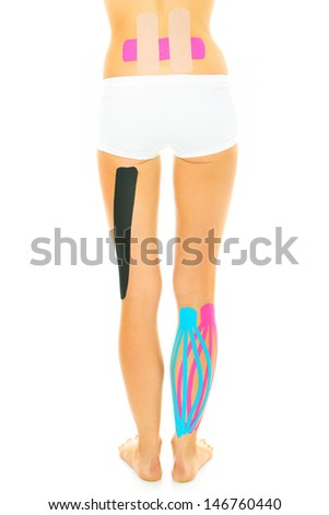 A picture of the back of a woman with physio tape on different parts of her body over white background