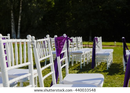 A picture of white chairs for guests decorated with violet cloth