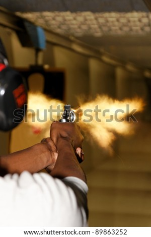A picture taken over the shoulder of a young man firing a gun at a shooting range in the precise moment of the muzzle flash. - stock photo