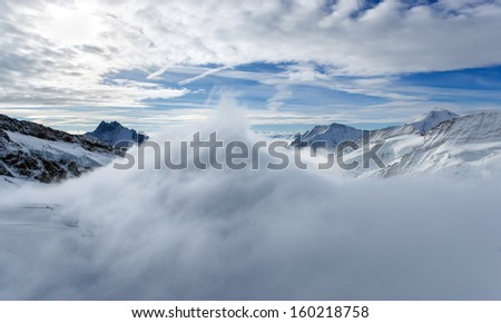 A picture with one of the highest mountains in the Alps, the peak over the clouds. / Above the clouds. - stock photo