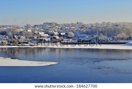 A picturesque small town covered with snow near the icy river