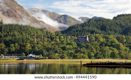 A picturesque view from the shore of Loch Leven looking over to Glencoe house on a sunny day. Ballachulish, Scotland.