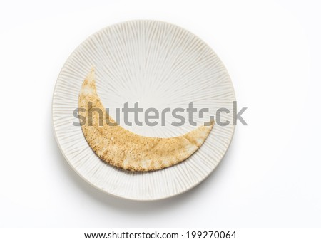 A piece of arabic bread (khaboos) cut into moon shape - stock photo