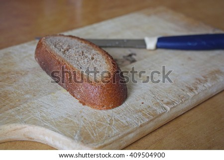A piece of black rye bread on a chopping board - stock photo