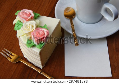 a piece of cake .a cup of coffee or tea .free text space paper note.Tasty soft creamy butter cake on a white plate over wooden background. tree colorful creamy roses decorated on top of butter cake.   - stock photo