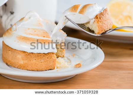 a piece of cake with a lemon on a fork (shallow DOF) - stock photo