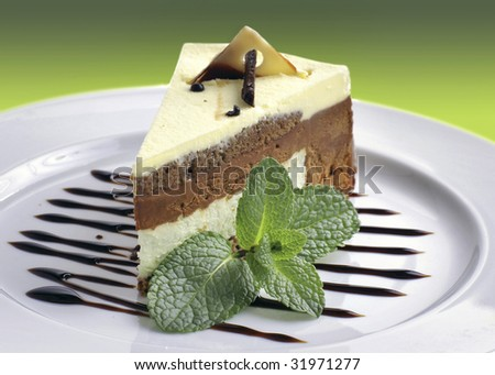 A piece of cake with a sprig of mint is on a plate.