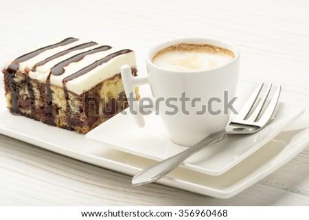 A piece of cake with cherry and chocolate and a cup of coffee on the white wooden background.