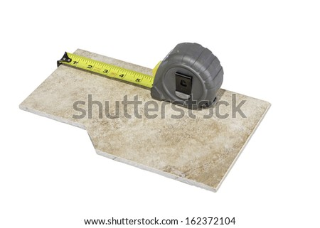 A piece of ceramic tile being measured with a tape measure isolated on a white background. - stock photo