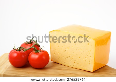 a piece of cheese with tomato on the board - stock photo
