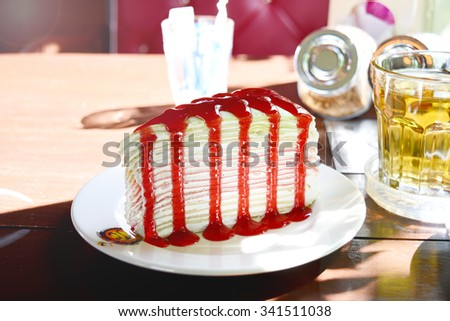 a piece of crepe cake with strawberry sauce and a glass of hot tea on a wood table - stock photo