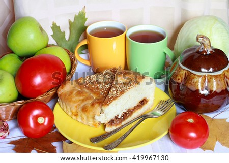 A piece of delicious fresh baked cabbage pie (tart, pasty, cake, calzone) with sesame on the yellow plate serving with red tomatoes, green apples, pumpkin, two cups of tea, foliage and vintage forks - stock photo