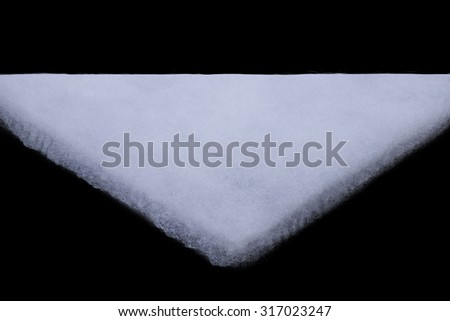 a piece of fabric from insulation batting triangular shape on a black background