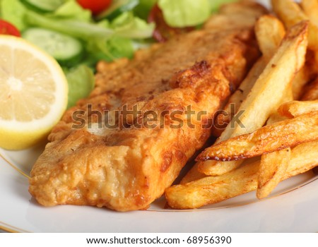 A piece of fish in batter served with french fried potato chips, lemon and a lettuce, rocket, cucumber and tomato salad.